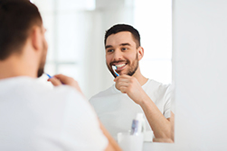 A man brushing his teeth with tips he learned at Sunnyside Dentistry in Clackamas, OR