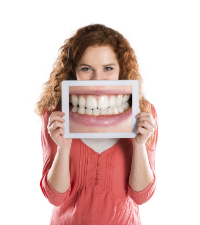 Woman with enlarged image of teeth learning about dentistry