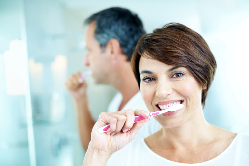 A woman using a toothbrush recommended by Sunnyside Dentistry in Clackamas, OR